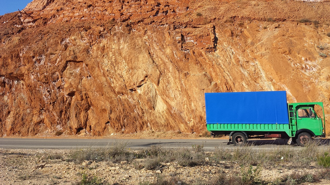 A blue and green lorry drives past a mine